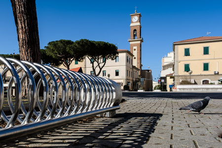 CECINA, TUSCANY, ITALY - March 31, 2018: piazza Carducci better known also as the children's square with the park to have fun and in the background the bell tower of the church of the Cathedral of San Giuseppe Editorial