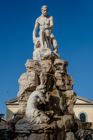 CECINA, TUSCANY, ITALY - March 31, 2018: Piazza Francesco Domenico Guerrazzi with the fountain of the Maremma Assetata created by the artist Emidio Vignali in 1919. The work represents Hercules that overshadows and dominates the Muses of bronze