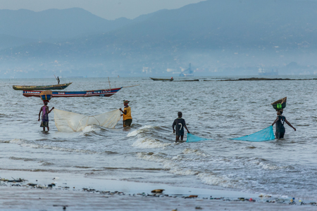 Yongoro, Sierra Leone - May 30, 2013: West Africa, four unknown fishermen pull fishing nets at the beaches of Yongoro in front of the capital of the Sierra Leone, Freetown