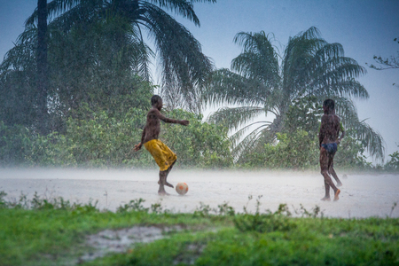 Yongoro, Sierra Leone - June 03, 2013: unknown boys play football during the rain in the village in front of the capital Freetown, SIerra Leone