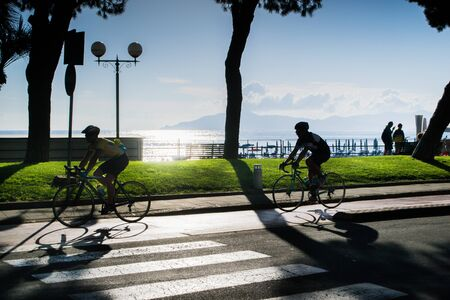 SESTRI LEVANTE, GENOA, ITALY - JUNE 1, 2018: two unknown cyclists near the waterfront and in the background view of the promontory of Portofino, Liguria, Italy