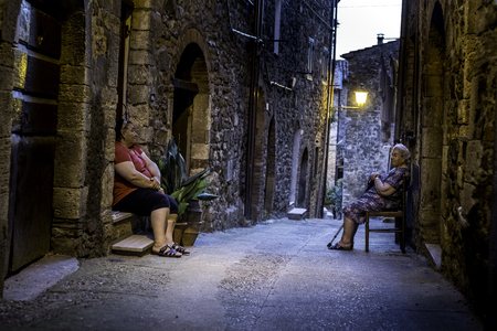 MONTEMERANO, GROSSETO, ITALY - JULY 29, 2018: Two unknown woman, Montemerano, Tuscany - small medieval village inMaremma. Montemeranois a 12th century town in the heart of Maremma, at 55 kilometers from Grosseto, Italy