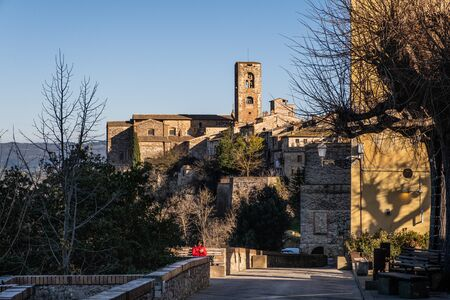 COLLE VAL D'ELSA, ITALY - DECEMBER 26, 2018: Unknown woman and panoramic view with the towers of the church of Santa Caterina and the Praetorian Palace of the medieval village of Colle di Val d'Elsa, Siena, Tuscany Editorial