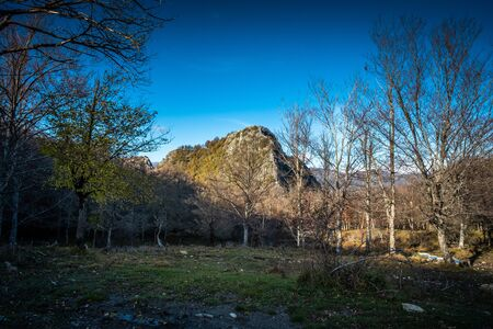 The Penna of Lucchio rock formation seen by Pracchie with autumn colors, walking along the Lucchese Apennines, Lucca - Tuscany, Italy 写真素材