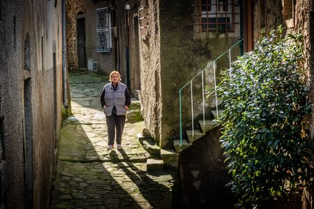 Excursion walking along the Lucchese Apennines, unknown woman in the village of Pontito, the narrow street of Santa Lucia, Lucca - Tuscany, Italy