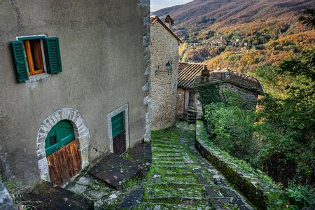 Excursion walking along the Lucchese Apennines, in the village of Pontito the narrow street of Santa Lucia, om background the town of Stiappa - Tuscany, Italy 写真素材