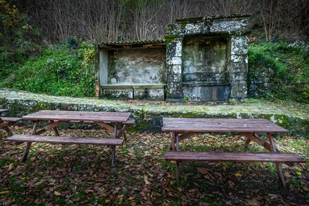 Fountain with two wooden benches in the village of Pontito in Via Santa Lucia under the cemetery, walking along the Lucchese Apennines, Lucca, Tuscany - Italy