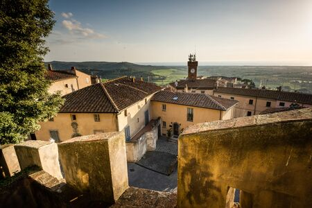 The ancient village of Castagneto Carducci seen from the castle with the civic tower and in the background the town of Donoratico and the Tyrrhenian sea. Tuscany, Italy