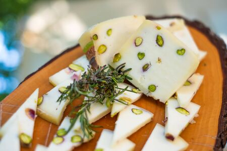 Processed italian cheese with rosemary, pistachios and grapes for aperitifs, compounds and preparations for tastings