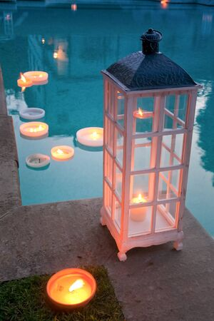 Glass containers for candles and swimming pool as holiday parties