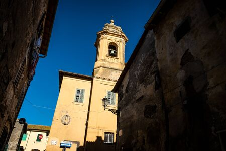 The bell tower and the facade of the Church of Santissima Maria Assunta in Montalto di Castro enclosed between the coasts of the Tyrrhenian sea, the waters of the Fiora river and the countryside of the Maremma Latium