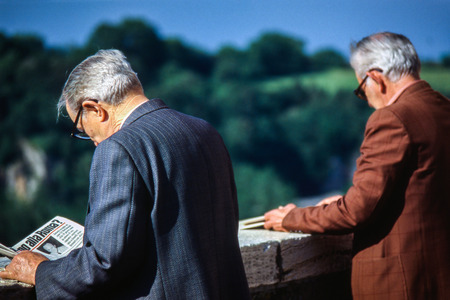 PITIGLIANO, ITALY - AVRIL 20, 1986: unknown elderly people read the newspaper in the city center, Tuscany, Italy