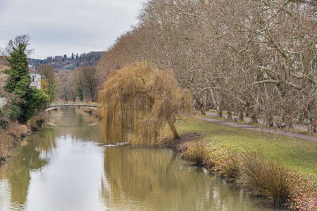 Winter view of the River Neckar and the Neckarinsel island from the popular Eberhardsbrucke with a weeping willow by the riverbank. Leafless trees conveys tranquility and calmness - Tubingen, Germany