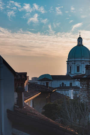 Villa 's roofs at sunset on a hill in the city (Colle Cidneo) with Cattedrale di Santa Maria Assunta (St Mary Cathedral) convey architectural concept. Italian lifestyle illustration - Brescia, Italy