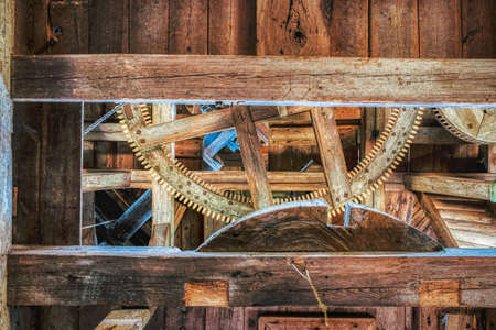 Solid wooden beam supports wooden cog and gears in an old windmill for wheat grinding. Old technology gearwheel in a rural wind mill in a wooden interior drives ancient grindstone for flour production