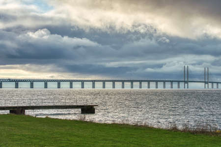 Dramatic capture of the Oresund Bridge or Oresundsbron conveys the profound link between the Scandinavian countries of Denmark and Sweden as spectral clouds hover over the bridge across the Baltic sea