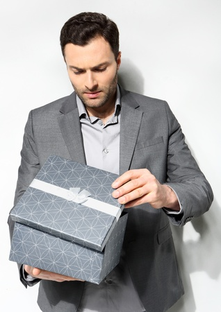 Office clerk with gift box on gray background Stock Photo - 18495521