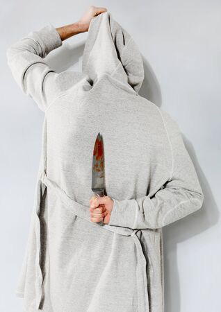 Man with a bloody knife on a gray background photo