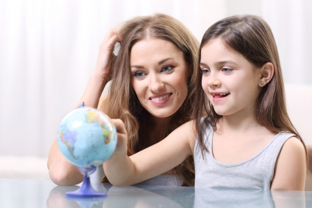 generational: Mother and daughter looking at a globe  Stock Photo