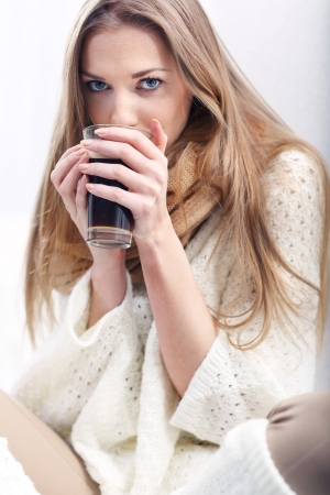 long socks: Long-haredi blonde with a cup of coffee sitting on a sofa Stock Photo