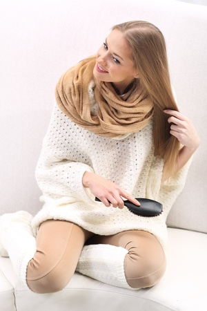 long socks: Smiling young woman combing her hair sitting on the sofa