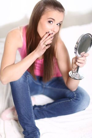 girl sit: Young long-haired blonde girl sitting on the bed and looks at the mirror