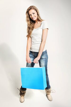 Beautiful lady holding blue shopping bag on white background Stock Photo - 18498144