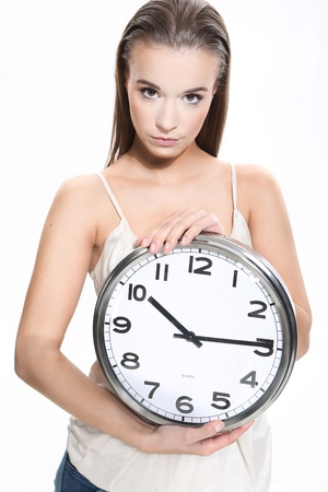 Girl with a clock on white background photo