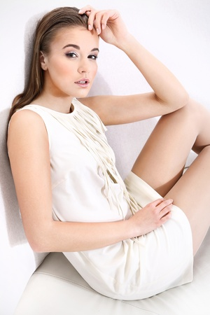 interrior: Beautiful girl in white dress sitting on a sofa next to a white wall