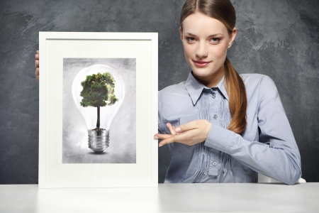 Girl holds a frame with the image of Eco concept, green tree growing in a bulb photo