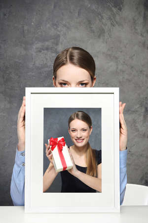 Girl holds a picture of a girl and a gift Stock Photo - 18497716