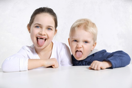 Brother and sister stick out tongues Stock Photo