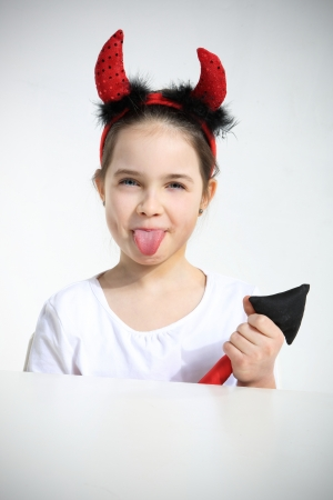 imp: Portrait of little girl dressed as pretty imp showing a tongue Stock Photo