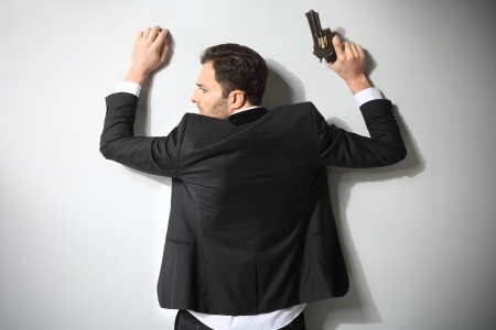 cuffed: Arrested man with gun, hands on wall Stock Photo