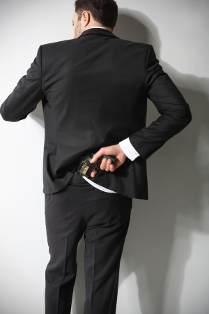 A man conceals a firearm in the back of his pants