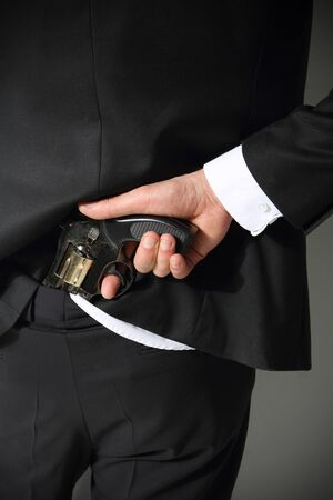 concealed: A man conceals a firearm in the back of his pants