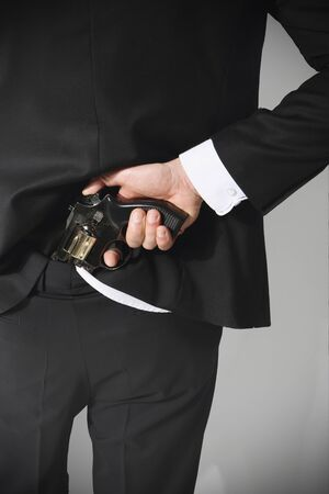 A man conceals a firearm in the back of his pants  photo