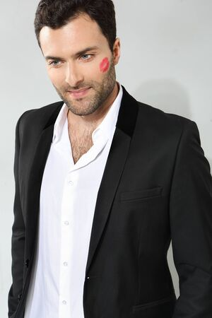 Young caucasian businessman with lipstick kiss mark on his cheek photo