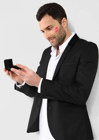 Attractive man looking at black box with cufflinks photo