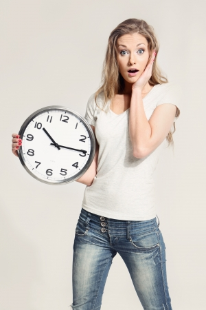 Surprised attractive young woman holding big clock Stock Photo - 18570568