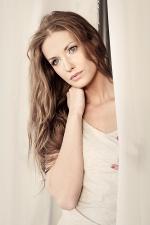 Beautiful girl looking through the curtains photo