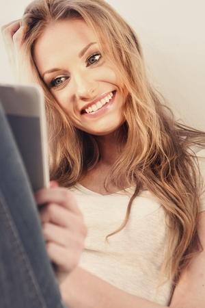 Beautiful girl reading e-book photo