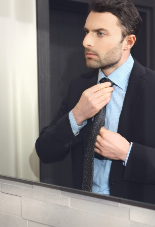 enticement: The young man looks at himself in the mirror and adjusts his tie