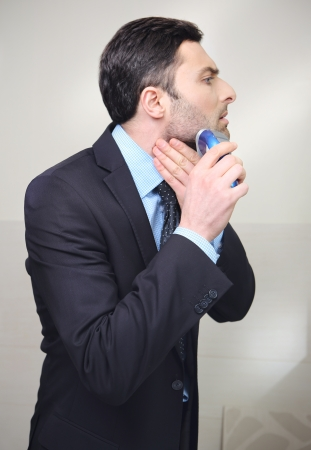 Young man shaving with electric razor photo