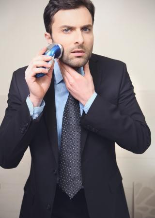 hombre afeitandose: Hombre joven afeitado con maquinilla de afeitar el�ctrica