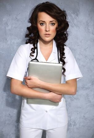 Woman doctor carrying a laptop photo