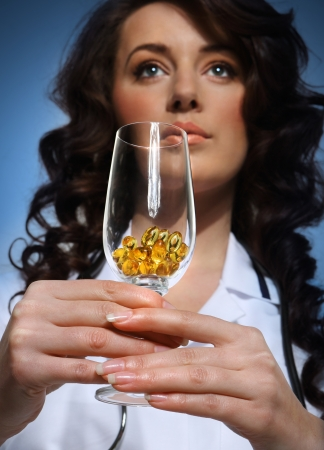 Doctor holding a glass with pills photo