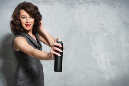 hairspray: Beautiful girl laying fixes using hairspray Stock Photo