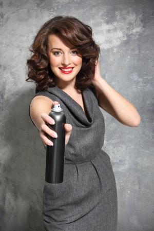 snips: Beautiful girl laying fixes using hairspray Stock Photo