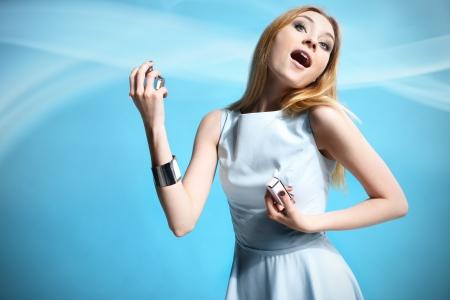Beautiful woman applying perfume on her body over white photo